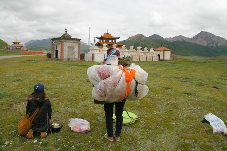 kneel down: GUOLUO, CHINA - JULY 26: Mother and daughter kneel down before white stupas in Gerisi temple when circle the holy mountain Anymachen on Tibetan Plateau.