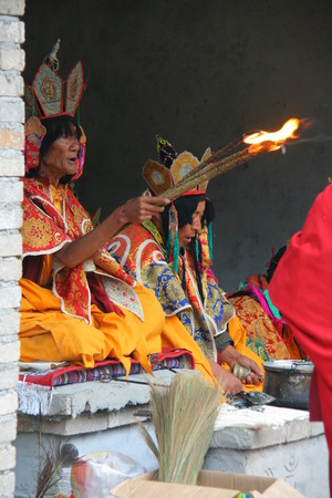 recite: LIJIANG, CHINA - SEPTEMBER 19: Lamas recite sutras to expiate the soul of the dead during a cremation ceremony of Mosuo Minority People, September 19, 2013, Yongning, Lijiang, China