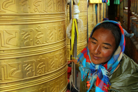 fanaticism: GUOLUO, CHINA - JULY 26: Woman rotates big prayer wheel in a small temple on Tibetan Plateau. July 26, 2013, Guoluo, Qinghai, China