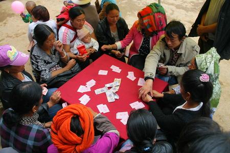 sit around: LIJIANG, CHINA - SEPTEMBER 19: Mosuo Minority People sit around a table and play gold flower, September 19, 2013, Yongning, Linlang, Lijiang, Yunnan, China Editorial