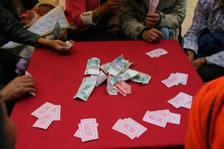 sit around: LIJIANG, CHINA - SEPTEMBER 19: Mosuo Minority People sit around a table and play cards, September 19, 2013, Yongning, Linlang, Lijiang, Yunnan, China Editorial