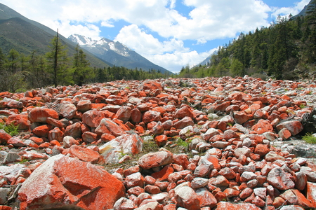 explained: Red stones landscape in Riwuqie, could be explained by red lichen, bacteria, or mineral Stock Photo