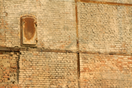 security gap: rusty iron gate in the wall, closeup