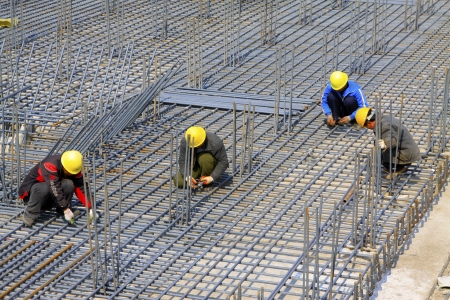 binding reinforcement mesh workers at a construction site, north china