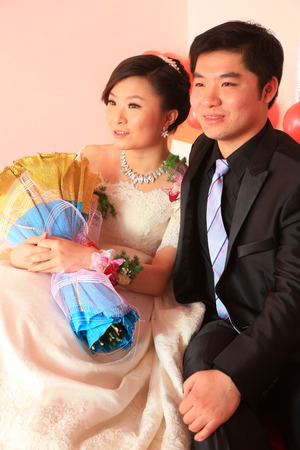 unrestrained: LUANNAN COUNTY - DECEMBER 29: A young couple sitting together, look forward to a better life in the future, in chinese wedding, on december 29, 2013, Luannan County, Hebei Province, China.  Editorial