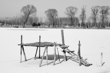wooden support on a pond after a snow Stock Photo - 27191554