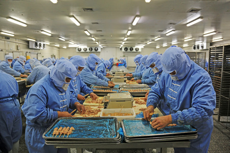 Workers in a meat processing production line, in a food processing enterprise, on December 20, 2013, tangshan city, hebei province, China.