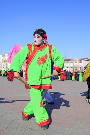 LUANNAN COUNTY - FEBRUARY 10: Old man holding pairs of wooden stick performing yangko dance in the street, during the Chinese Lunar New Year, February 10, 2014, Luannan County, Hebei Province, China. 新聞圖片