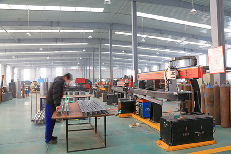 TANGSHAN - DECEMBER 22: The worker in operating machinery on the production line, in a solar equipment production workshop on december 22, 2013, tangshan, china.