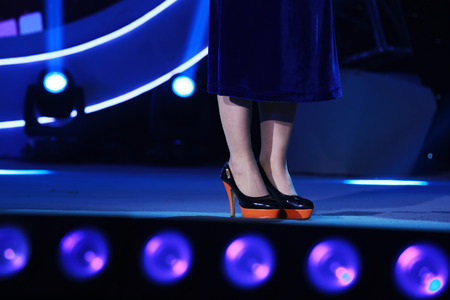 female legs wearing high heeled shoes on the stage photo