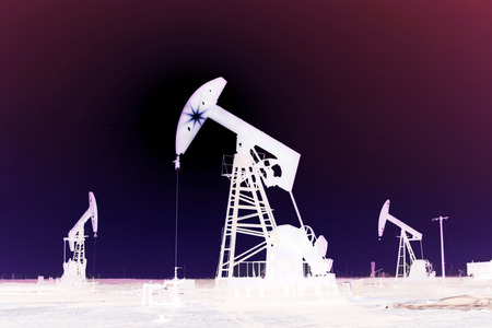 digitization: CAOFEIDIAN - DECEMBER 1: The crank balanced beam pumping unit under the curtain of night in the JiDong oilfield, on December 1, 2013, caofeidian, hebei province, China.