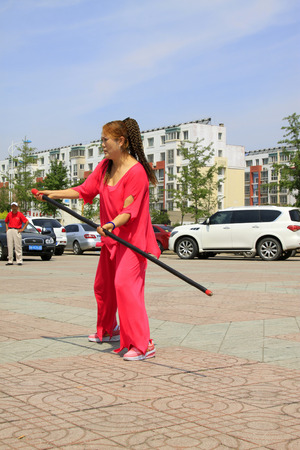LUANNAN COUNTY - JUNE 29: woman in red was performing stick fencing in the square, on june 29, 2014, LuanNan county, hebei province, China