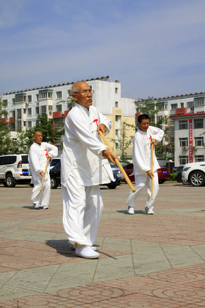 LUANNAN COUNTY - JUNE 29: A group of people were performing stick fencing on the gym in the square, on june 29, 2014, LuanNan county, hebei province, China