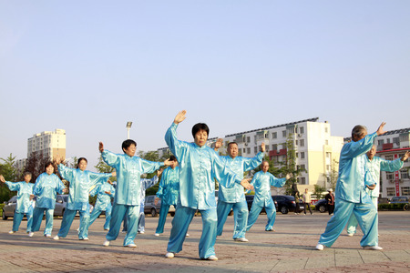 LUANNAN COUNTY - JUNE 14: A group of people were performing Tai chi chuan on the gym in the square, on june 14, 2014, LuanNan county, hebei province, China  新闻类图片