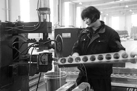 mechanization: TANGSHAN - DECEMBER 22: The worker in operating machinery on the production line, in a solar equipment production workshop on december 22, 2013, tangshan, china.
