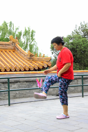 BEIJING - MAY 23: lady was kicking shuttlecock in the Beihai Park,on may 23, 2014, Beijing, China 新聞圖片