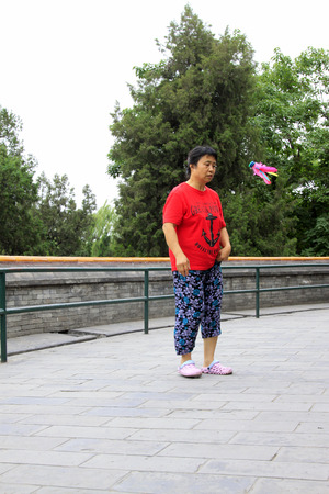 ms: BEIJING - MAY 23: lady was kicking shuttlecock in the Beihai Park,on may 23, 2014, Beijing, China
