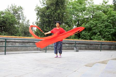 BEIJING - MAY 23: lady was Waving red silk cloth in the Beihai Park,on may 23, 2014, Beijing, China