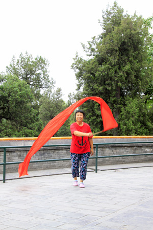ms: BEIJING - MAY 23: lady was Waving red silk cloth in the Beihai Park,on may 23, 2014, Beijing, China