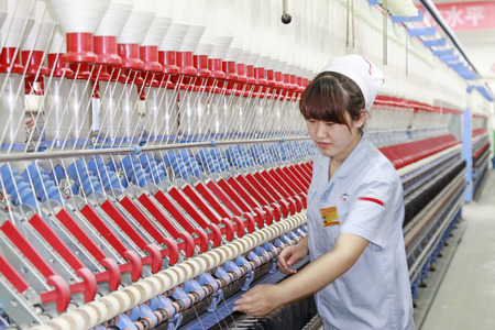 mechanization: LUANNAN - MAY 4: Women were spinning production line operation in production workshop, on May 4, 2014, Luannan county, hebei province, China.  Editorial