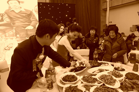 wedding customs: LUANNAN COUNTY - DECEMBER 29: The bride and groom together to flip a fish on the dining table, traditional customs in chinese wedding, on december 29, 2013, Luannan County, Hebei Province, China.