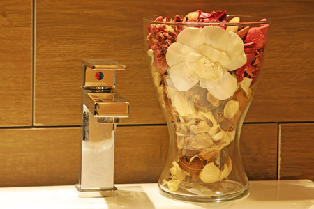 fiori secchi: bicchiere di fiori secchi e rubinetto in acciaio inox, primo piano di foto