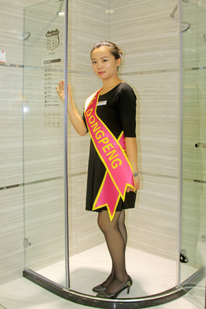 TANGSHAN CITY - SEPTEMBER 13: A female clerk to introduce customers to glass in the bathroom, on september 13, 2014, Tangshan City, Hebei Province, China
