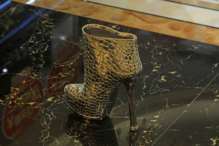 meticulous: Modelling of aureate high-heeled shoes, closeup of photo Stock Photo