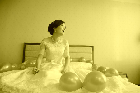 wedding customs: LUANNAN COUNTY - DECEMBER 29: The bride sat on the bed, waiting for the arrival of the groom, traditional customs in chinese wedding, on december 29, 2013, Luannan County, Hebei Province, China.