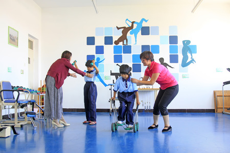 LUANNAN COUNTY - SEPTEMBER 3: teacher helping disabled students to do rehabilitation training, in a rehabilitation school, on september 3, 2014, Luannan County, Hebei Province, China