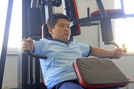 LUANNAN COUNTY - SEPTEMBER 3: A fat boy on exercise fitness equipment in school, on september 3, 2014, Luannan County, Hebei Province, China