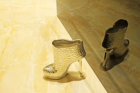 aureate: Modelling of aureate high-heeled shoes, closeup of photo Stock Photo