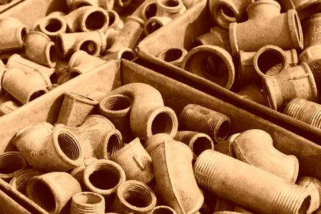 Metal plumbing pipe fittings piled up in the box  in a market Stock Photo