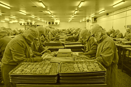 food processing: Workers in a meat processing production line, in a food processing enterprise, on December 20, 2013, tangshan city, hebei province, China.