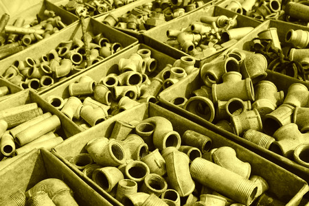 castings: Metal plumbing pipe fittings piled up in the box  in a market Stock Photo