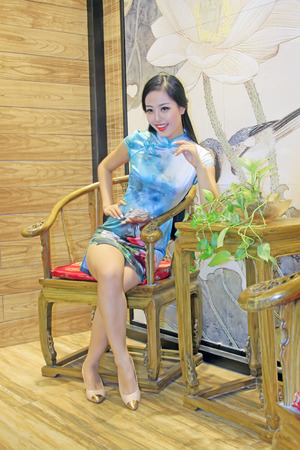 table skirt: TANGSHAN CITY - SEPTEMBER 13: Female fashion models and traditional style tea table in a shop, On September 13, 2014, Tangshan City, Hebei Province, China Editorial