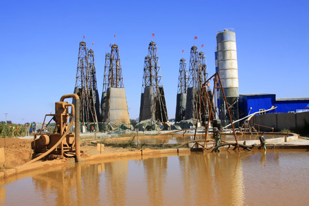sedimentation: LUANNAN COUNTY - OCTOBER 13: Drilling rig derrick and yellow water in MaCheng iron mine, on october 13, 2014, Luannan County, Hebei Province, China Editorial
