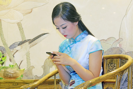 tangshan city: TANGSHAN CITY - SEPTEMBER 13: Beauty model checking mobile phone on a cane chair, On September 13, 2014, Tangshan City, Hebei Province, China Editorial