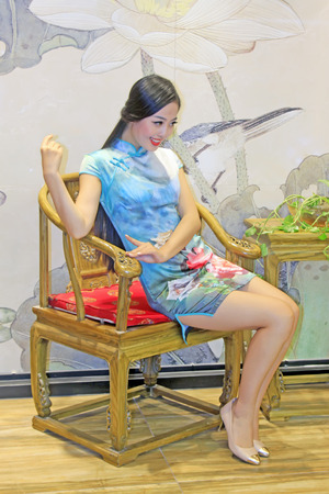 tangshan city: TANGSHAN CITY - SEPTEMBER 13: Female fashion models and traditional style furniture in a shop, On September 13, 2014, Tangshan City, Hebei Province, China Editorial