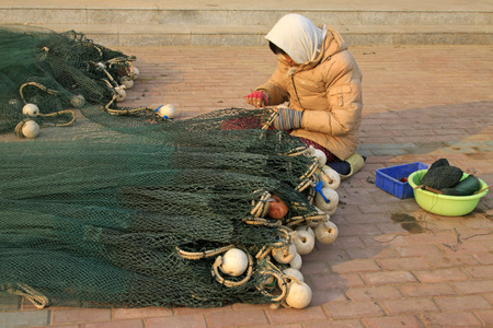 chinese fishing nets: LUANNAN COUNTY - DECEMBER 27:  A woman was repairing nets on December 27, 2014, Luannan County, Hebei Province, China