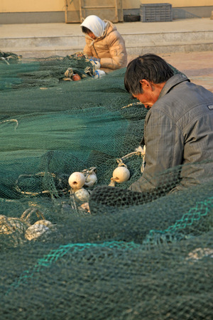 chinese fishing nets: LUANNAN COUNTY - DECEMBER 27: fishermen repairing nets on December 27, 2014, Luannan County, Hebei Province, China Editorial