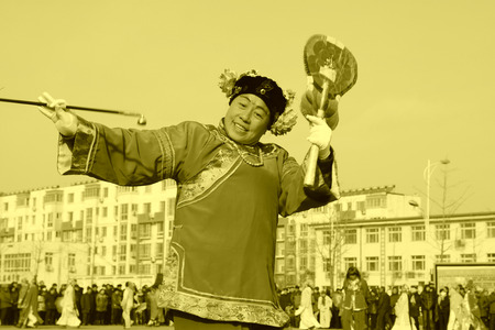 buffoon: LUANNAN COUNTY - FEBRUARY 11: Buffoon wearing colorful clothes, performing yangko dance in the street, during the Chinese Lunar New Year, February 11, 2014, Luannan County, Hebei Province, China.