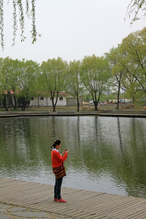 tangshan city: TANGSHAN CITY - APRIL 18: A lady dress in red standing by the lake, April 18, 2015, Tangshan City, Hebei Province, China