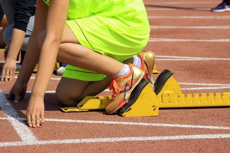 starting block: yellow starting block and athletes, closeup of photo