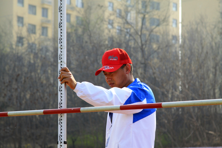 athletic wear: LUANNAN COUNTY - APRIL 14: Referee adjustment height at the sports meeting, April 14, 2015, Luannan County, Hebei Province, China Editorial