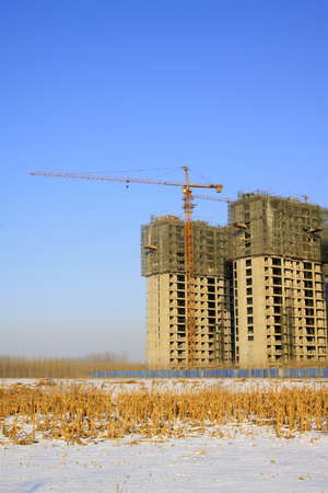 agricultural engineering: Unfinished buildings and tower crane, closeup of photo