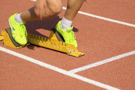 starting blocks: Starting blocks and the athletes leg, closeup of photo