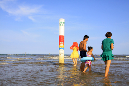the surge: JINGTANG PORT - AUGUST 29: several tourists visiting nearby storm surge alert water level mark, on August 29, 2015, Jingtang Port, hebei province, China.