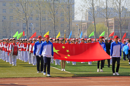 bearer: LUANNAN COUNTY - APRIL 14: China flag and flag bearer at the athletics meeting, April 14, 2015, Luannan County, Hebei Province, China