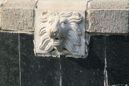 restore ancient ways: lion head carving in a park, closeup of photo